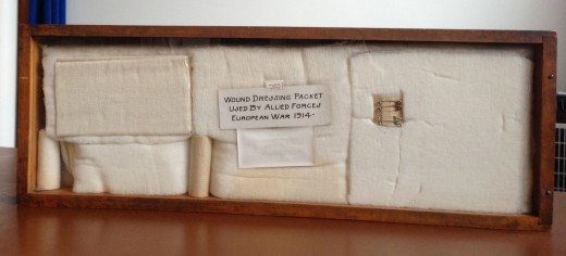 Shadowbox in our museum showing the Johnson & Johnson wound dressing packet for soldiers developed in 1914.